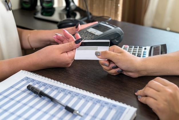 Kobiece ręce z kartą kredytową i terminalem