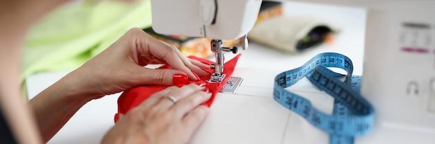 Kobiece ręce z manicure przyszywają czerwony materiał na maszynie do szycia krawcowa szyje ubrania w