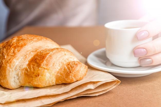 Kobiece ręce z manicure trzyma filiżankę kawy i jedzenie rogalika. śniadanie w stylu francuskim