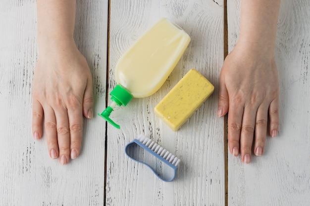 Kobiece ręce z mydłem w płynie, mydłem i szczotką do czyszczenia. umyj ręce