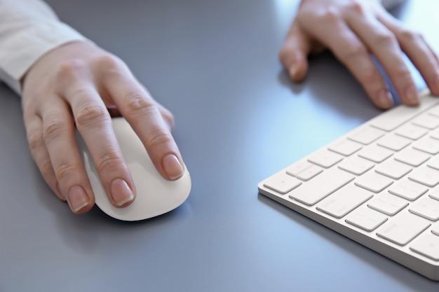 Kobiece ręce z myszką komputerową i klawiaturą na szarym stole