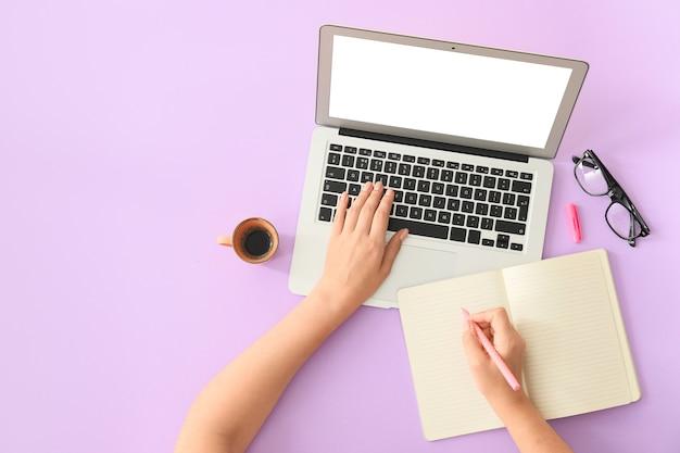 Kobiece ręce z nowoczesnym laptopem i notebookiem na kolorowej powierzchni