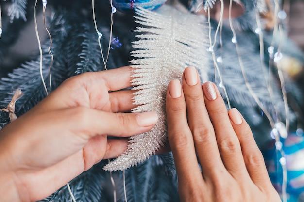 Kobiece ręce z projekt paznokci boże narodzenie nowy rok. nude beżowy lakier do paznokci, błyszczący złoty brąz na jeden palec