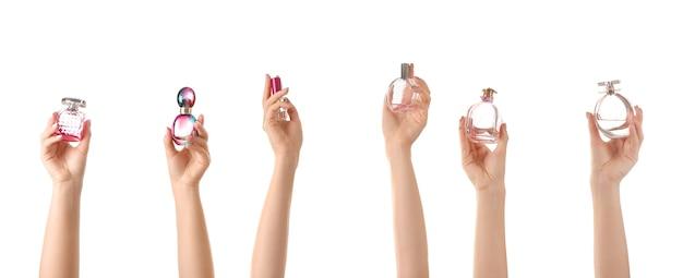 Kobiece ręce z różnych butelek perfum na białym tle
