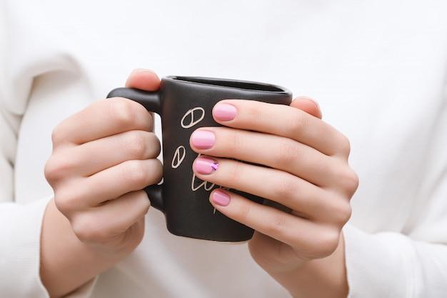 Kobiece ręce z różowy wzór paznokci trzymając czarny kubek.