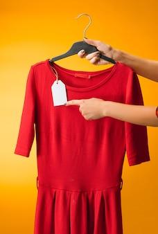 Kobiece ręce z sukienką na żółto. koncepcja zakupów i sprzedaży