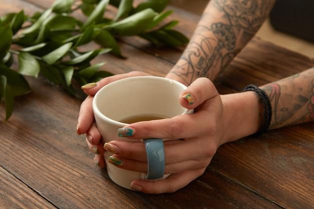 Kobiece ręce z tatuażami trzymając filiżankę kawy, gałąź zielonych liści na drewnianym stole.