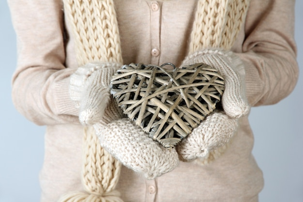 Kobiece ręce z wiklinowym sercem, zbliżenie