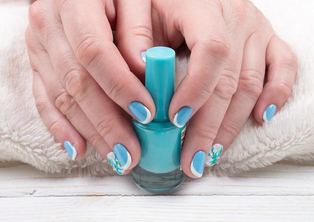 Kobiece ręce z wypielęgnowanych paznokci trzymając butelkę lakieru do paznokci