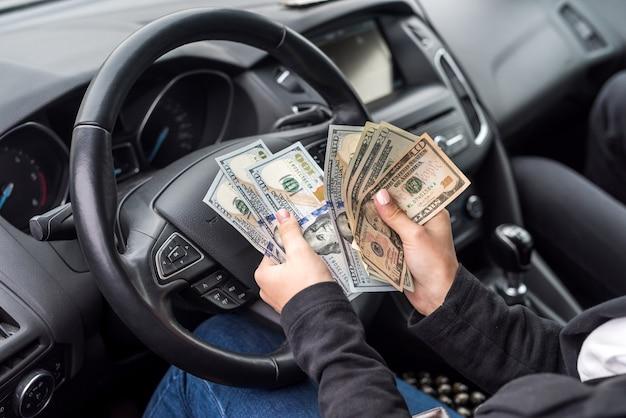Kobiece ręce z zbliżenie banknotów dolara na kierownicy
