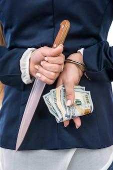 Kobiece ręce za plecami, ukrywanie noża i dolarów