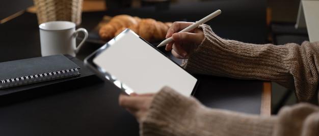Kobiece ręce za pomocą tabletu siedząc przy stole śniadaniowym z książkami harmonogramu, kawą i rogalikiem
