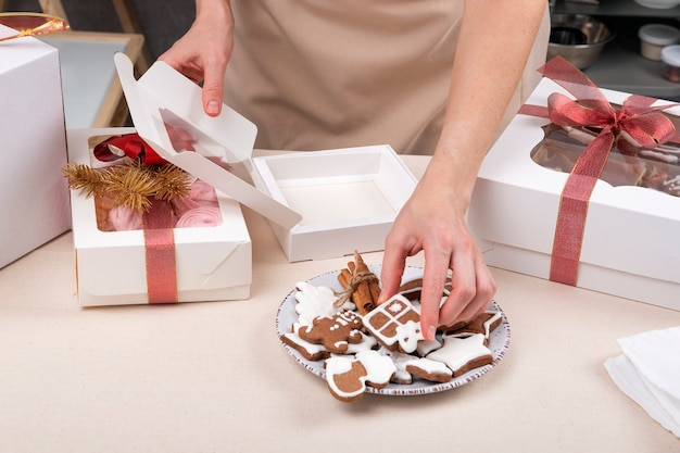 Kobiece ręce zawijają pierniki w ozdobne pudełko. ścieśniać.