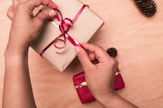 Kobiece ręce zawijające prezent na boże narodzenie, robiące czerwoną kokardkę w pudełku na papier rzemieślniczy na powierzchni drewna z szyszkami
