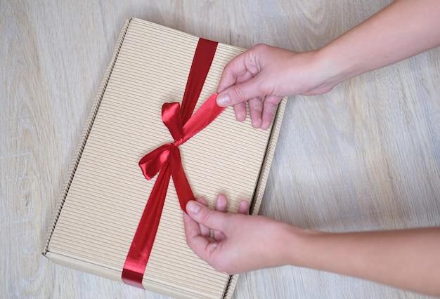 Kobiece ręce zbliżenie, trzymając prezent w pudełku z czerwoną wstążką.