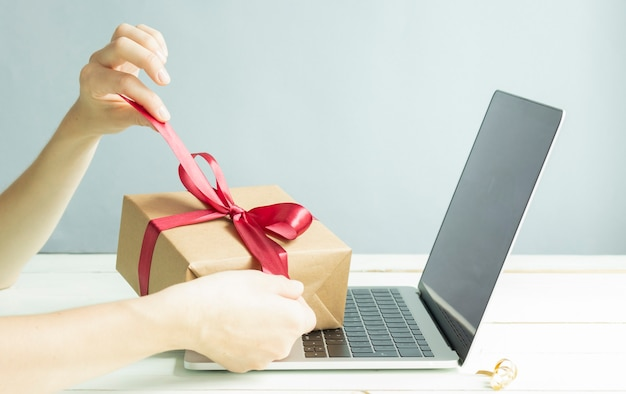 Kobiece ręce zdejmują czerwoną wstążkę z prezentu na biurku