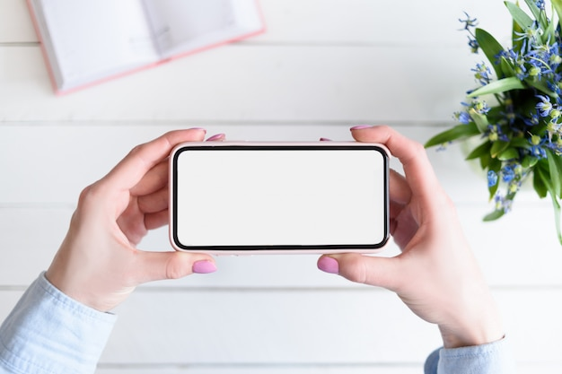 Kobiece ręce ze smartfonem. biały pusty ekran. stół z notatnikiem i kwiatami