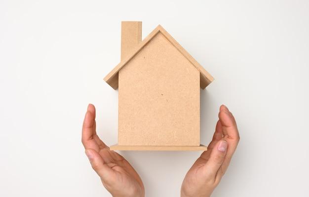 Kobiece ręce złożone do siebie na drewnianym miniaturowym modelu domu na białym tle. koncepcja ubezpieczenia nieruchomości, ochrona środowiska, szczęście rodzinne