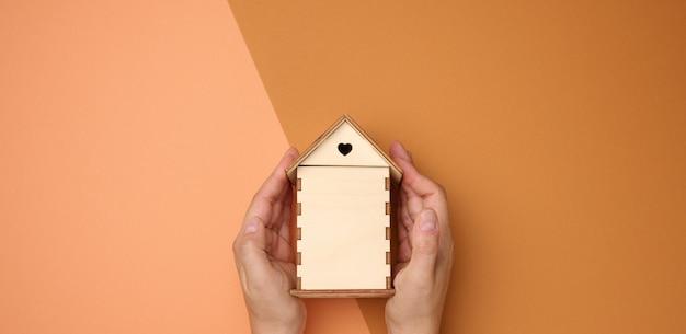 Kobiece ręce złożone do siebie na drewnianym miniaturowym modelu domu na brązowym tle. koncepcja ubezpieczenia nieruchomości, ochrona środowiska, szczęście rodzinne