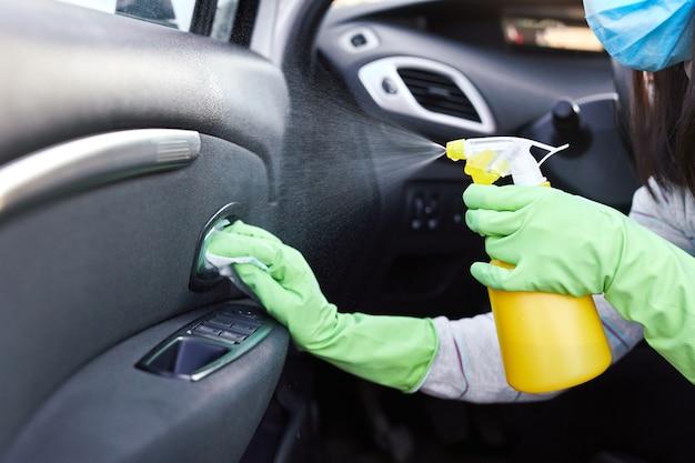 Kobiece ręczne natryskiwanie środków dezynfekujących i antyseptycznych mokrych chusteczek do dezynfekcji samochodu