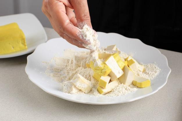 Kobiece ręczne powlekanie pokrojonego żółtego tofu z mąką, proces gotowania robienie chrupiącego tofu (tahu krispi) w kuchni