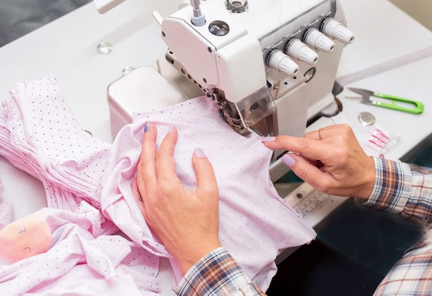 Kobiece ręczne szycie ubrań dla dzieci na maszynie owerlokowej, produkcja odzieży