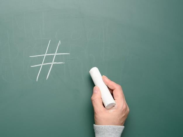 Kobiece ręcznie rysowane symbol hashtag białą kredą na tablicy kredą zieloną, z bliska