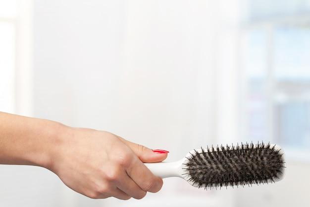 Kobiece ręki trzymającej grzebień fryzjerski w sklepie kosmetycznym
