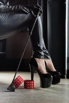 Kobiece seksowne nogi z kajdankami i batem do upraw