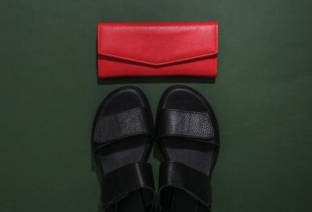 Kobiece skórzane czarne sandały i portfel na zielonym tle. widok z góry