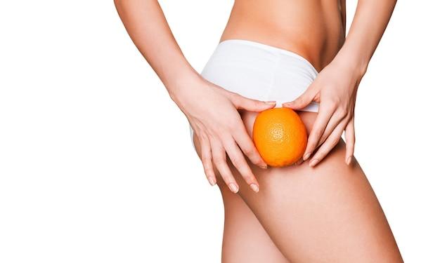 Kobiece smukłe ciało w sportowej bieliźnie trzyma pomarańczowy