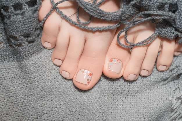 Kobiece stopy beżowym lakierem do paznokci na szarym materiale.