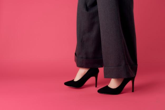 Kobiece stopy czarne buty przycięte widok różowe tło nowoczesny styl glamour