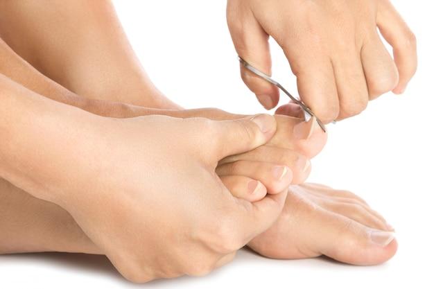 Kobiece stopy i nożyczki do paznokci