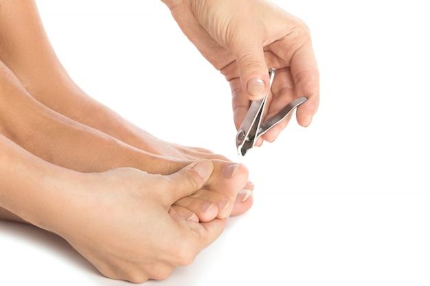 Kobiece stopy i obcinacz do paznokci