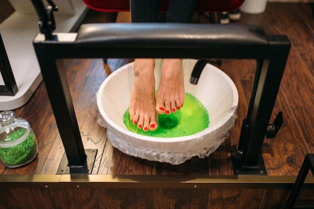 Kobiece stopy klienta w kąpieli pedicure, widok z góry
