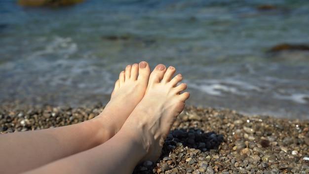 Kobiece stopy na tle fal morskich. kobieta leży na brzegu z małymi kamieniami blisko wody. koncepcja wakacje nad morzem. 4k uhd