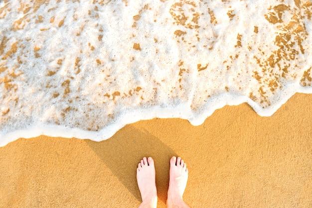 Kobiece stopy na żółtym piasku plaży z morską falą i białą pianką