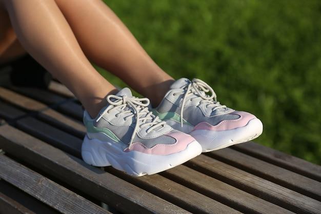 Kobiece stopy noszących sportowe trampki na zewnątrz