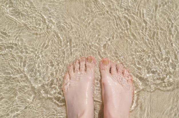 Kobiece stopy pod czystą wodą.