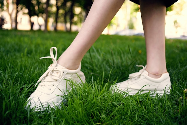 Kobiece stopy trawa park spacer na świeżym powietrzu