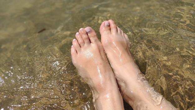 Kobiece stopy umyte falą morza. letni słoneczny dzień.
