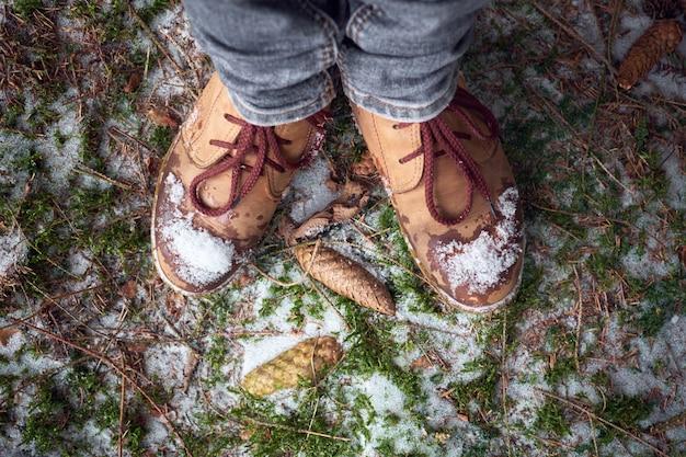 Kobiece stopy w butach podróżniczych na omszałej śnieżnej ziemi w zimowym lesie. koncepcja podróży.