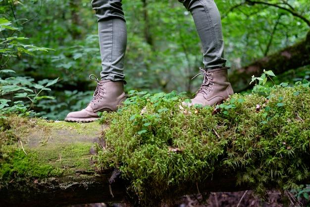 Kobiece stopy w butach podróżniczych na omszałym logu w lesie. koncepcja podróży.