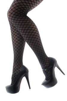 Kobiece stopy w czarnych butach i wzorzystych rajstopach
