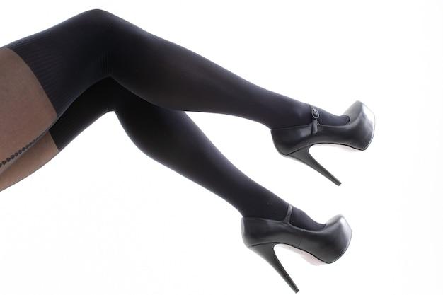 Kobiece stopy w czarnych butach na obcasie i rajstopach