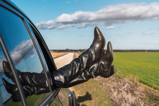 Kobiece stopy w kowbojskich butach wystające z okna samochodu z pięknym widokiem na zielone pola pod błękitnym niebem z chmurami