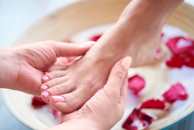 Kobiece stopy w misce z wodą i płatkiem