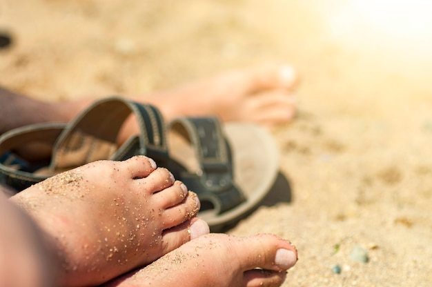 Kobiece stopy w piasku na plaży.