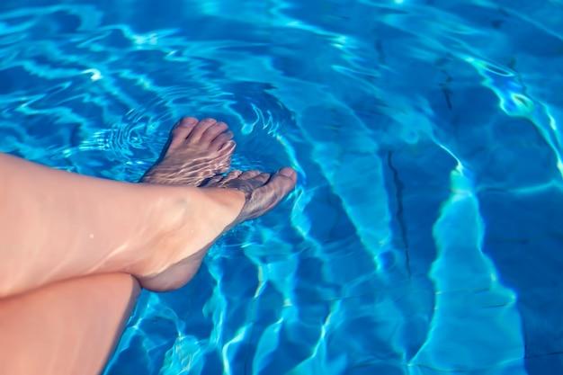 Kobiece stopy w wodzie. koncepcja wakacje i lato